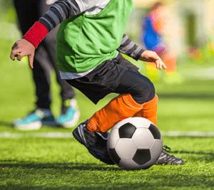 Poika pelaa jalkapalloa.