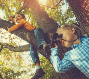 Pojat kiipeilevät puissa.