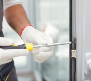 Kiinteistöpalvelu korjaamassa ovea