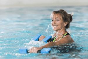 vesijumppaaja käsipainojen kanssa altaassa
