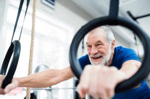 Seniorimies kuntoilee renkaissa kuntosalilla
