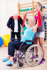 Pyörätuolissa oleva seniori kuntouttavassa fysioterapiassa
