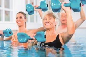 Seniorit jumppaavat altaassa käsipainoilla.