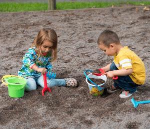 Päiväkodin lapset leikkivät hiekkalaatikolla.