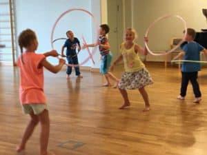 Lasten liikuntaleiriläiset jumppaavat vanteiden kanssa.