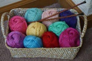 Värikkäitä villalankoja ja puikot korissa