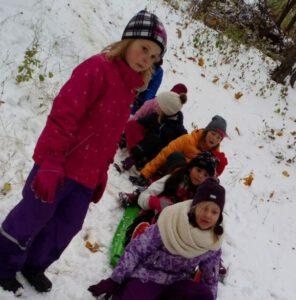 Koululaisten päiväleirille osallistuvat laskevat mäkeä Harjulassa.
