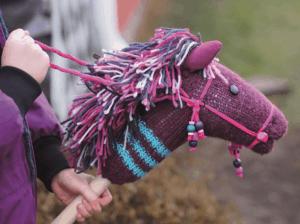 Lapsi ratsastaa käsityönä tehdyllä keppihevosella.