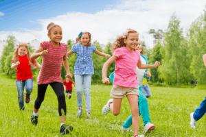 Lapset juoksevat nurmikolla kesäisenä päivänä.