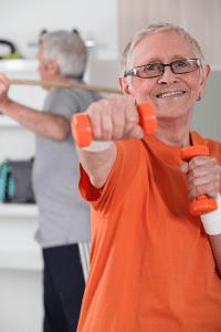 Seniori nyrkkeilee käsipainoilla.